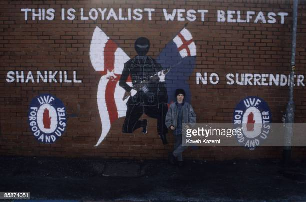 A boy standing in front of a mural celebrating the loyalist paramilitary organization the Ulster Volunteer Force in the predominantly Protestant and...