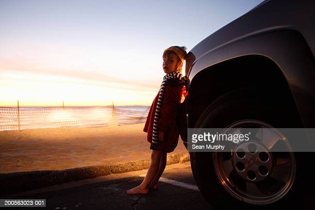 Boy (4-5) standing in front of car headlights on beach at sunset