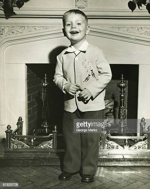 Boy (4-5) standing in front of fireplace, singing, (B&W)