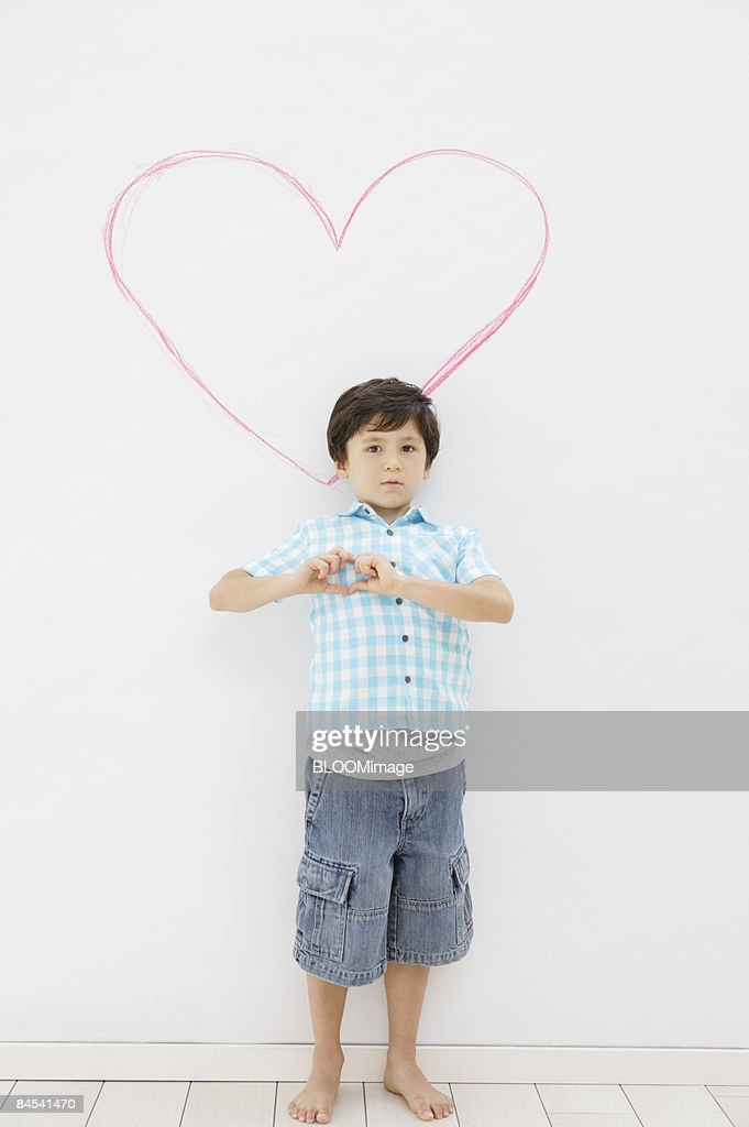 boy standing in front of heart drawing stock photo getty images