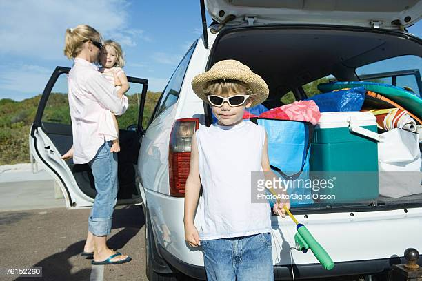 Boy standing in front of loaded car trunk