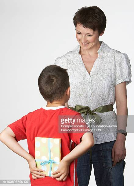 "boy (6-7 years) standing in front of mother, holding present behind back, studio shot - ""compassionate eye"" fotografías e imágenes de stock"