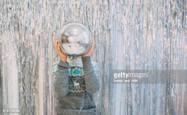 boy standing in front of silver tinsel decorated wall holding a giant christmas bauble - extra groot stockfoto's en -beelden