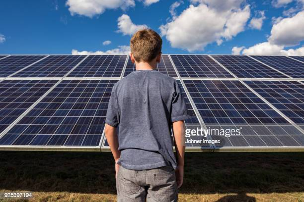 Boy standing in front of solar panels