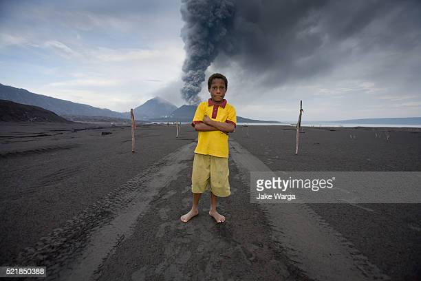 boy standing in front of volcano, mt. tavurvur, rabaul, papua new guinea - jake warga stock pictures, royalty-free photos & images