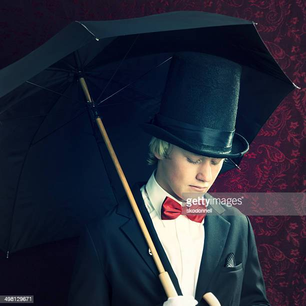 boy standing in front of wallpaper with umbrella - top hat stock pictures, royalty-free photos & images