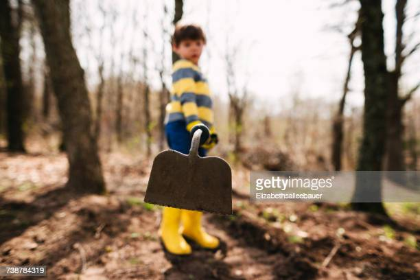 Boy standing in garden with a hoe