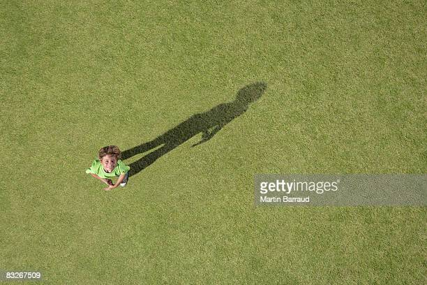 Boy standing in grass looking up