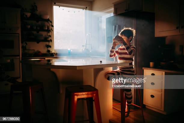 Boy standing in kitchen eating his breakfast in morning light