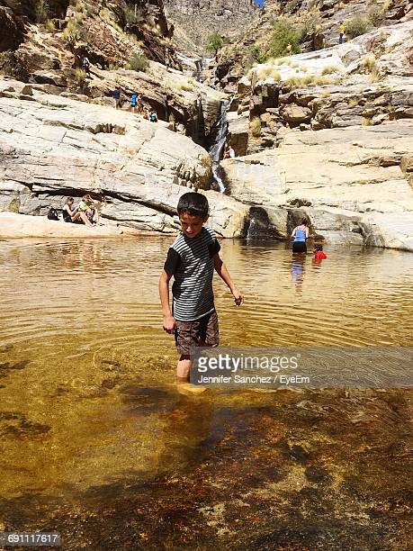 Boy Standing In Lake Against Rocky Mountain