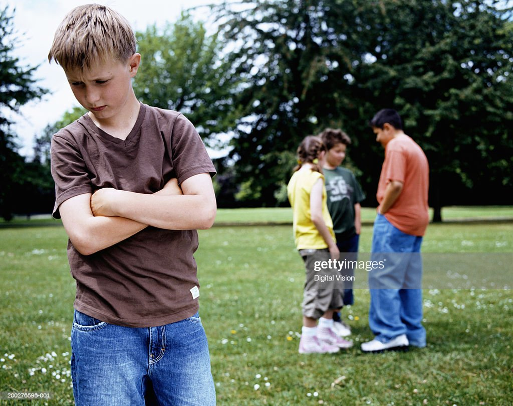 Boy (9-11) standing in park, arms crossed, group (10-12) in background : Stock Photo