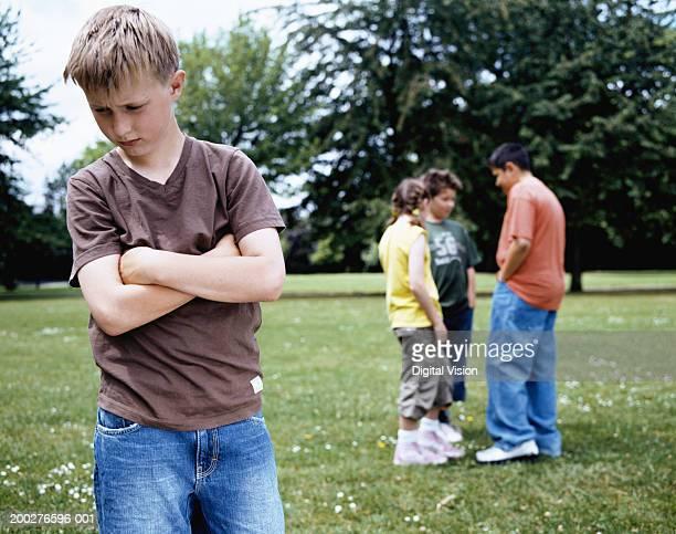 boy (9-11) standing in park, arms crossed, group (10-12) in background - 10 11 jahre stock-fotos und bilder