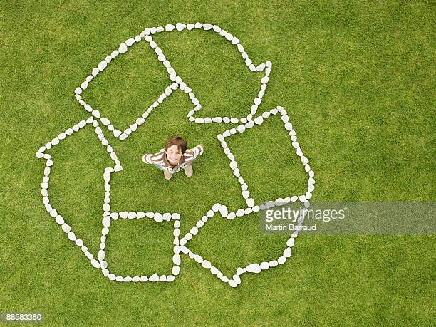 Boy standing in recycling symbol made of rocks