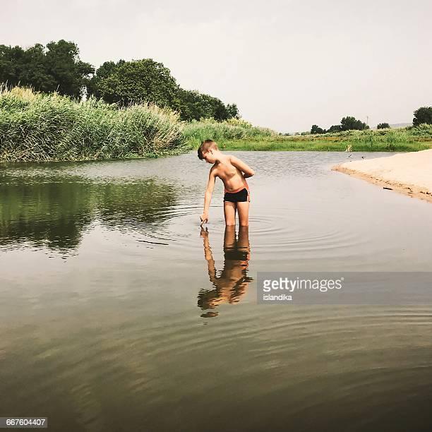 Boy standing in river
