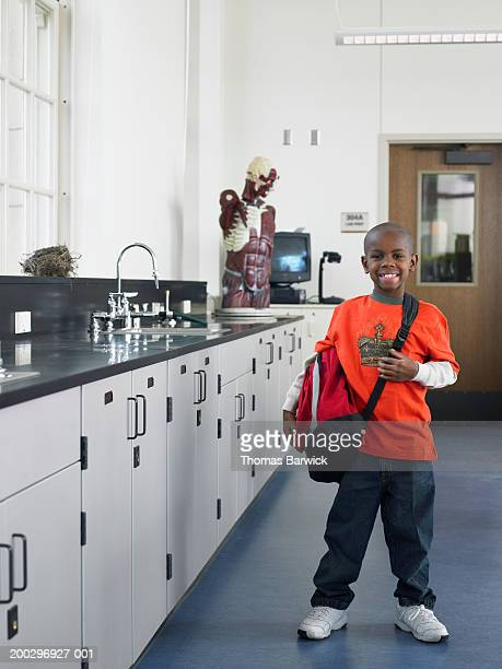 boy (6-8) standing in school laboratory, smiling, portrait - shoulder bag stock pictures, royalty-free photos & images