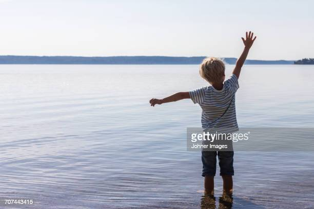 Boy standing in sea with arms raised