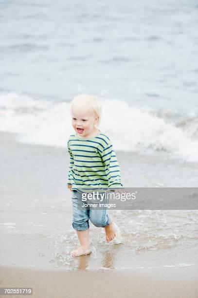 Boy standing in surf on beach