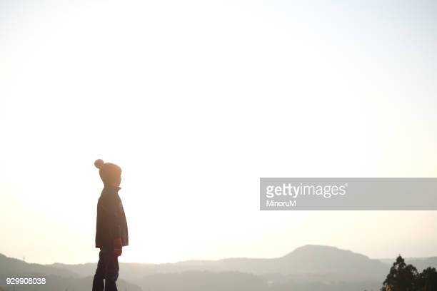 Boy standing in the morning glow