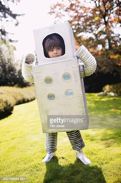 Boy (3-5) standing in yard, wearing robot costume
