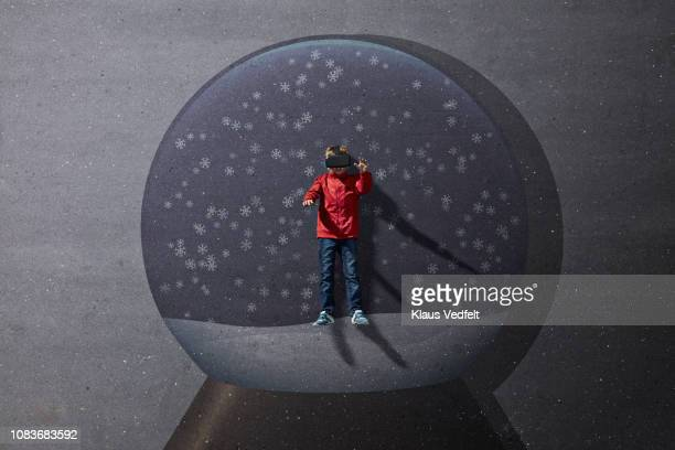Boy standing inside imaginary painted Christmas snow globe