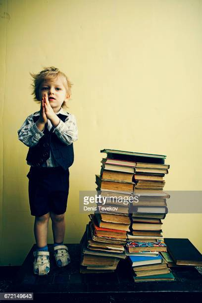 Boy standing near stacks of books