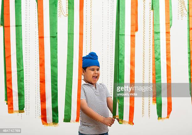 Boy standing near tricolor scarf's and laughing