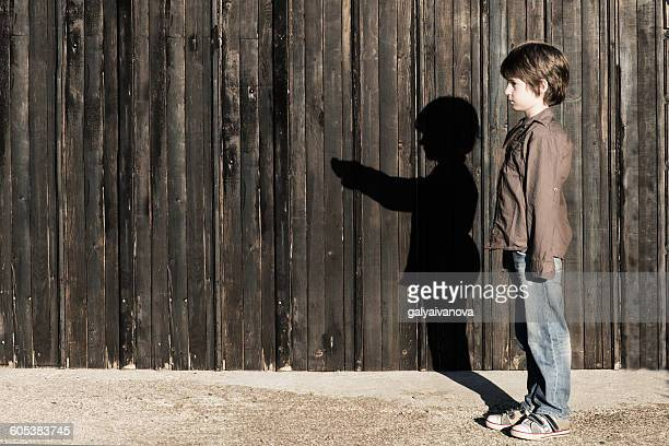 Boy standing next to a wooden fence with alter ego shadow