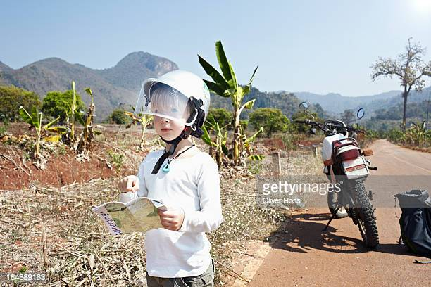 Boy standing next to motorbike on country road