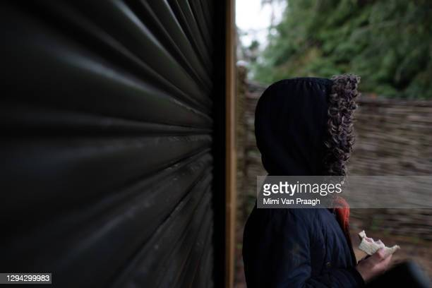 boy standing next to shutters, hood up eating a sandwich. - criminal stock pictures, royalty-free photos & images