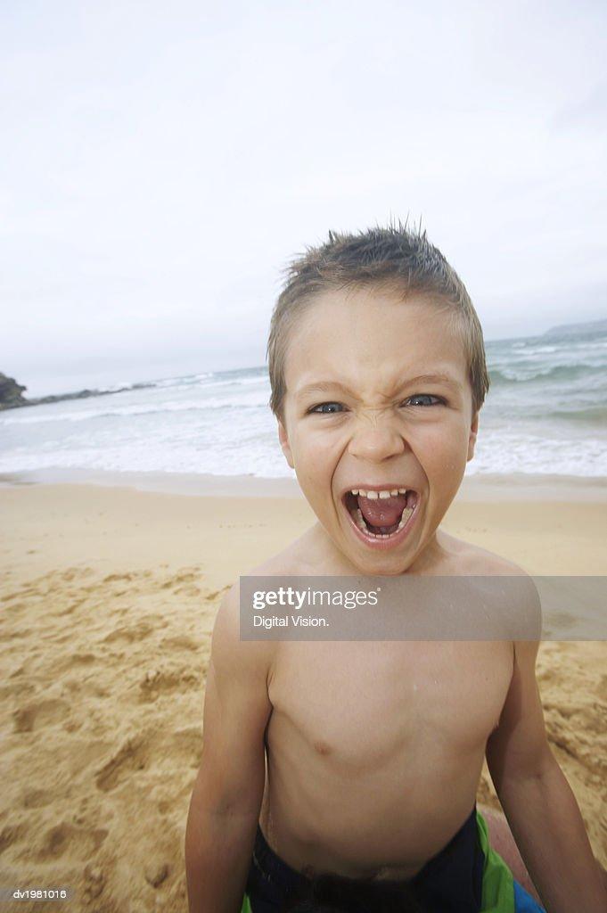 Boy Standing on a Beach Shouting : Stock Photo