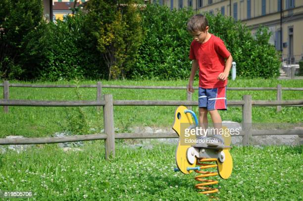 Boy standing on a spring rider at playground
