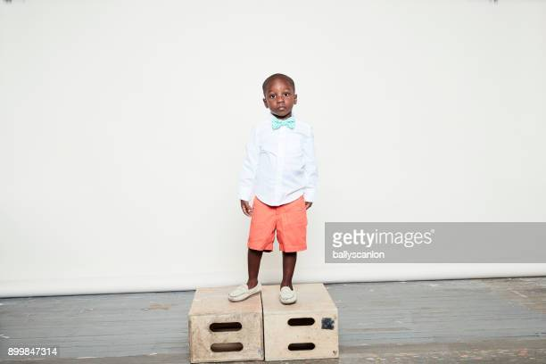 Boy Standing On Apple Box, Studio Portrait
