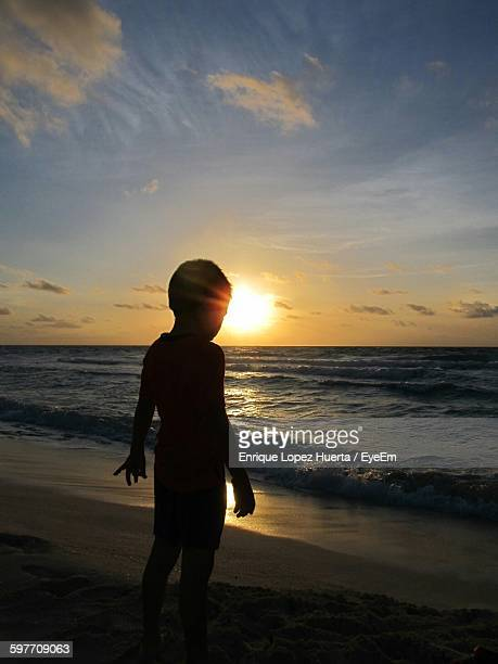 boy standing on beach against sky during sunset - lopez stock pictures, royalty-free photos & images