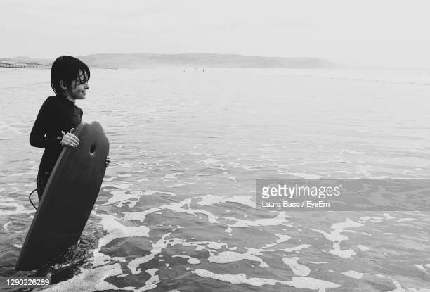 boy standing on beach against sky - black and white stock pictures, royalty-free photos & images