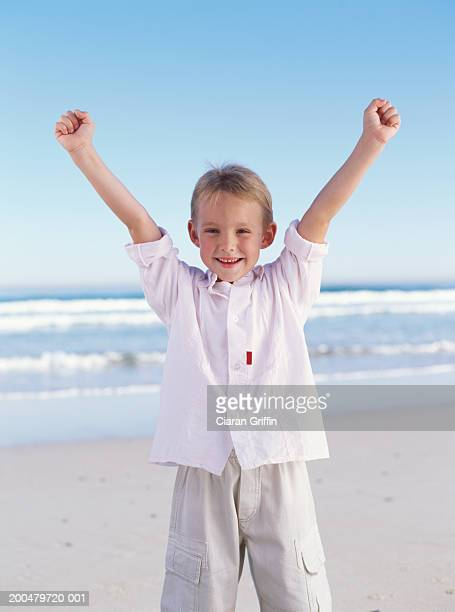 Boy (10-12) standing on beach, arms raised, smiling, portrait