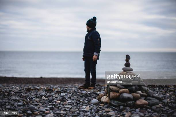 Boy standing on beach by a stack of pebbles, Ireland