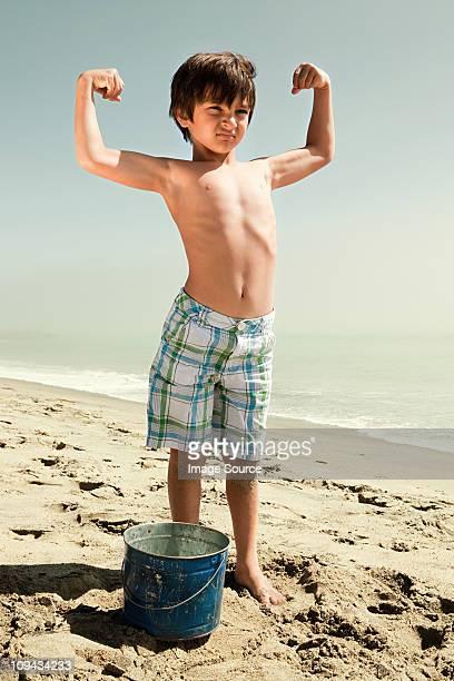 boy standing on beach flexing muscles - spieren spannen stockfoto's en -beelden
