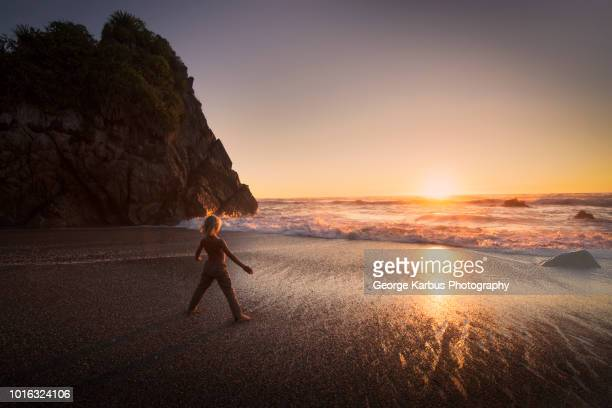 boy standing on beach, looking at sunset, kaikoura, gisborne, new zealand - gisborne stock photos and pictures