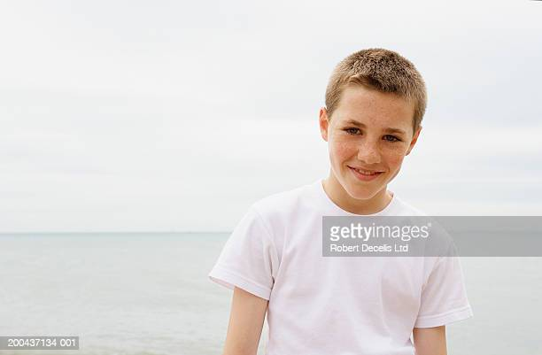 Boy (11-13) standing on beach, smiling, portrait