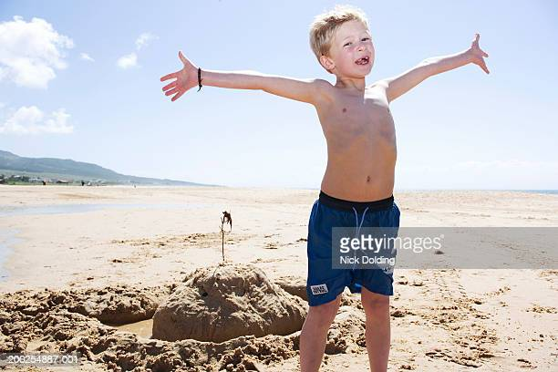 Boy (8-10) standing on beach with outstretched arms, portrait
