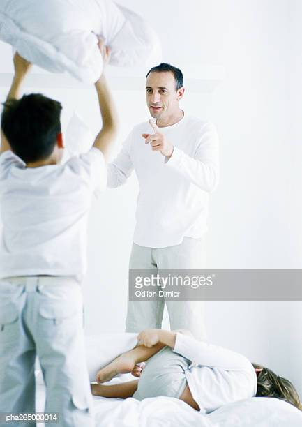 Boy standing on bed holding up pillow, rear view, second boy lying on bed, man pointing at first boy