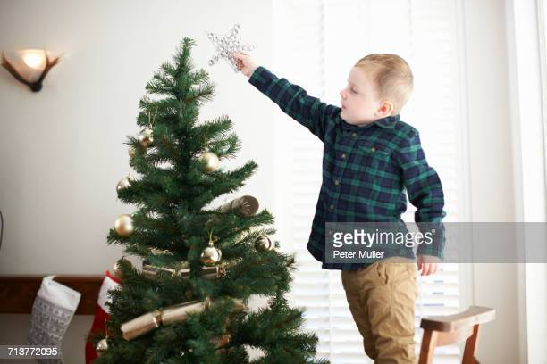 Boy standing on chair to place star on christmas tree