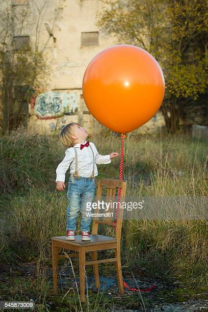 Boy standing on chair with balloon on meadow