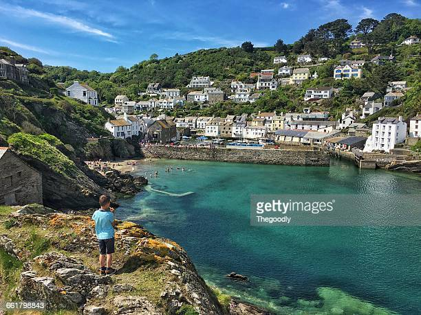 Boy standing on cliff looking at village, Polperro, Cornwall, England, UK