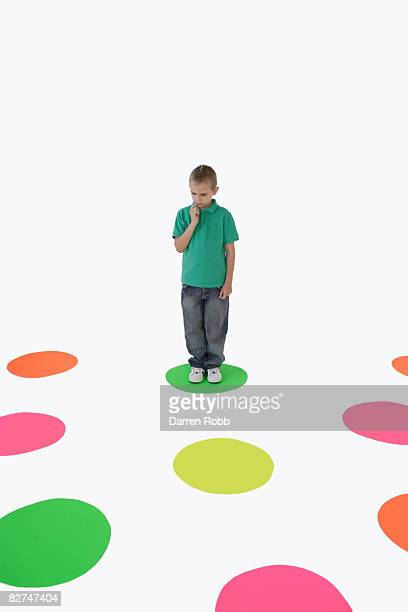 Boy standing on coloured circle contemplating