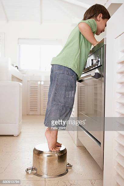 Boy standing on cooking pot