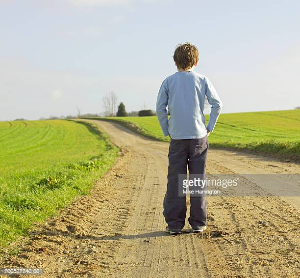 Boy (8-10) standing on country road, rear view