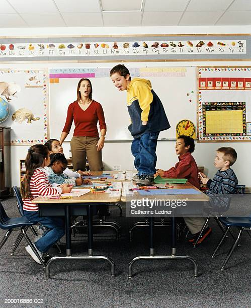 Boy (5-7) standing on desk in front of class