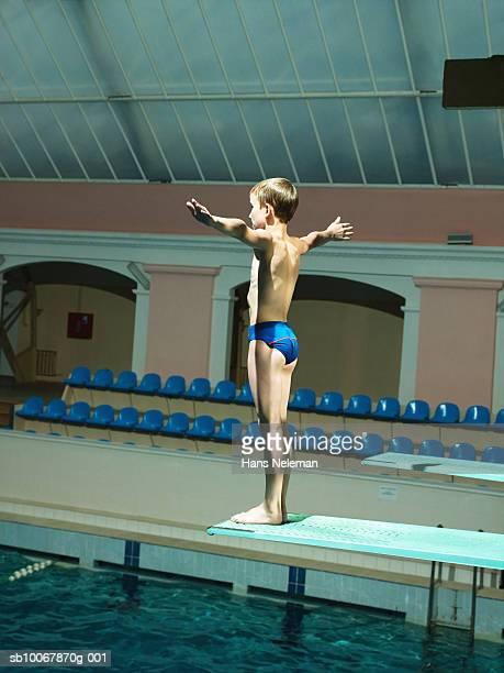 Boy (8-9) standing on dive platform