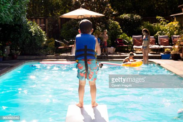 boy standing on diving board - diving board stock pictures, royalty-free photos & images
